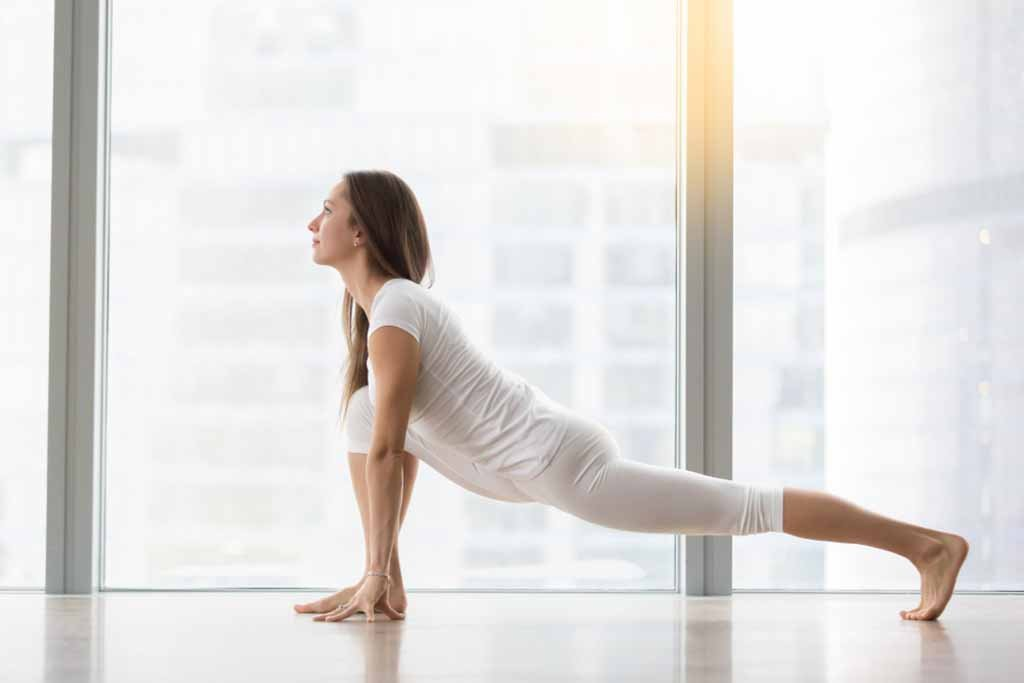 Woman is performing Low Lunge Yoga pose